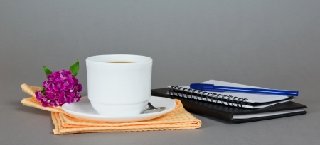 Cup of coffee with a saucer, a spoon and a flower on a napkin, a sketchpad and the ball-point on a gray background photo