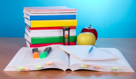 scientific literature: The open book with bookmarks, exercise book a pen and markers, a pile of the closed books a hourglass and apples on a table