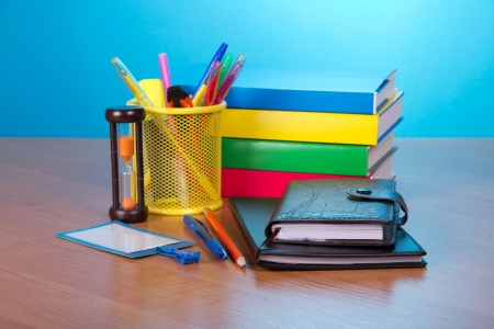 Organizer, notepad, books, blank badge, pens in a support, and hourglasses on a table photo