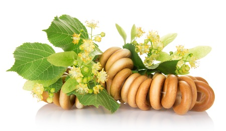 The bagels connected by a rope, and  linden flowers, isolated on white photo