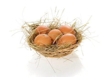 bast basket: Eggs, hay in a bast basket, isolated on white Stock Photo