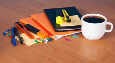 A set of office accessories, the diary, exercise books, blank for notes  and a cup of coffee on a table photo