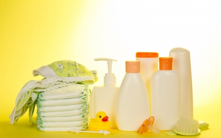 sensitive skin: Childrens toilet accessories, coif and diapers, on a yellow background