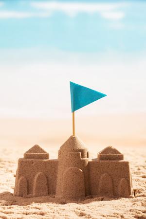 모래와 바다의 배경에 플래그 근접에서 성.