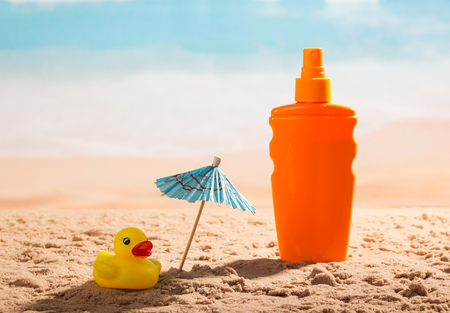 Sunscreen, umbrella and a rubber duck in the sand against the sea.