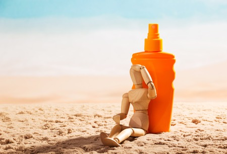 figurine: Wooden mannequin and sunscreen at the beach.