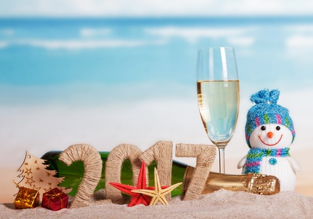 Figures 2017 champagne bottle and glass, snowman, Christmas tree, starfish, gifts in the sand against the sea. 版權商用圖片 - 65358565