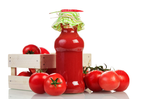 Wooden box with tomatoes, juice bottle and red pepper isolated on white background.