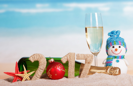 Christmas ball instead of the number 0 in the amount of 2017 champagne bottle and glass, snowman and starfish in the sand against the sea.