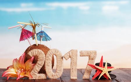 calendario diciembre: Figuras 2.017 coco, estrellas de mar y flores en la mesa contra el mar. Foto de archivo