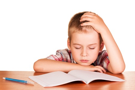 the weariness: Tired boy sitting at the table fell asleep on exercise book isolated on white background.