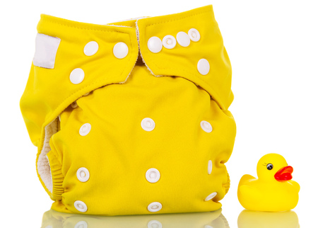 Modern eco-friendly diaper and rubber duck isolated on white background.