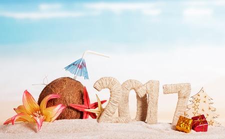 calendario diciembre: Coco, número 2017, estrellas de mar, flor, el árbol y los regalos de Navidad en la arena contra el mar. Foto de archivo