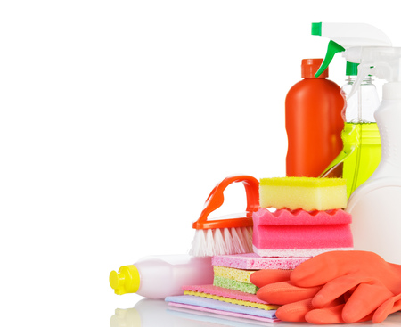 Bottles with cleaners, rubber gloves, sponge and brush isolated on white background.