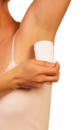 hygeine: An unknown woman uses a dry underarm deodorant isolated on white background.