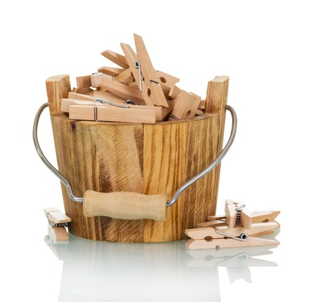 Bucket with wooden clothespins close-up isolated on white background.