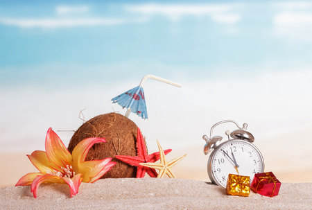 Coconut, starfish, flower and gifts alarm clock in the sand against the sea.