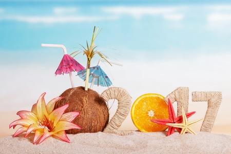 calendario diciembre: Parte de naranja en lugar del número 0 en la cantidad de 2017, de coco, estrellas de mar y de la flor en la arena contra el mar. Foto de archivo