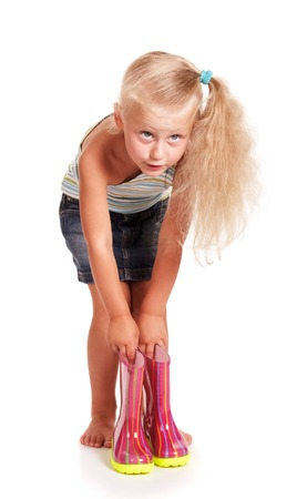 Little blond girl in a skirt and blouse bending down holding rubber boots isolated on white background.