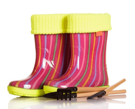 inset: Children rubber boots with fabric inset, shovel and rake isolated on white background. Stock Photo