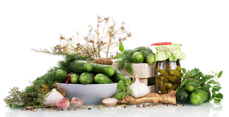 A wooden crate and a bowl of green cucumbers, jar of pickles, spice isolated on white background.
