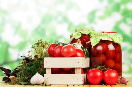 Wooden box of fresh tomatoes, jars Pickled tomatoes and spices on an abstract green background.