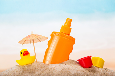 Sunscreen, umbrella and tos in the sand against the sea. Stock Photo