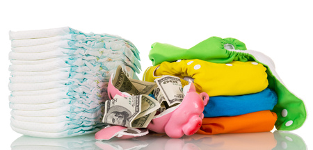 incontinence: Stacks of disposable, cloth diapers and broken piggy bank with dollars isolated on white background. Stock Photo