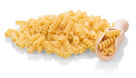 helical: A pile of helical macaroni in a wooden scoop isolated on white background.
