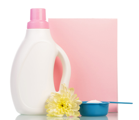 A pack of washing powder in a measuring cup, a bottle of liquid, flower isolated on white background.