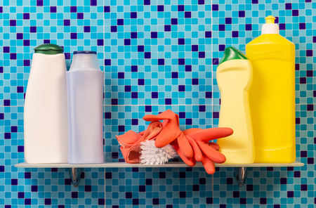 rubber gloves: Shelf with bottles of detergent, rubber gloves and brush on an abstract blue background.