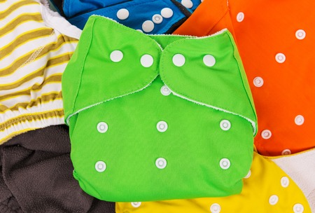 Lots of colorful eco-friendly diapers are scattered. Background.