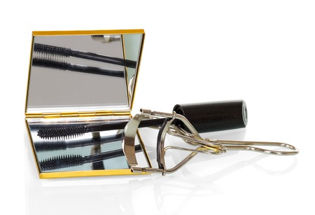 curling: Hand mirror, mascara and curling eyelashes isolated on white background.