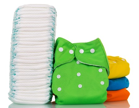 incontinence: A stack of disposable and cloth diapers isolated on white background.