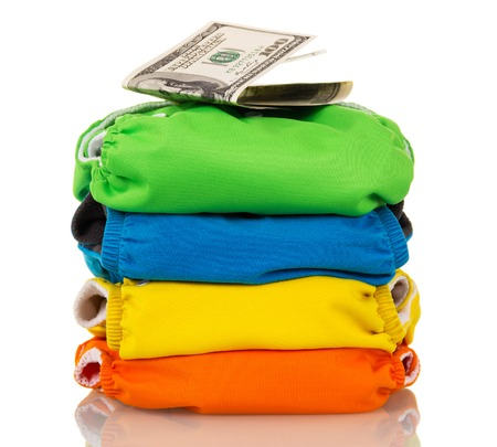 A stack of modern cloth diapers and dollars isolated on a white background.