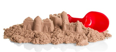 Sand Castles of kinetic sand and shovel isolated on white background.