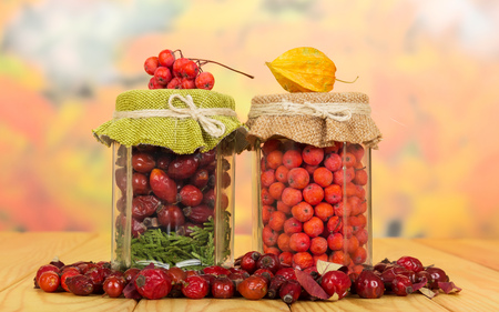 mountain ash: Jars with berries of mountain ash and wild rose on a background of autumn leaves