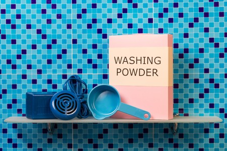 measuring spoon: Shelf with ultrasonic washing machine, a pack of washing powder, measuring spoon on abstract blue background. Stock Photo