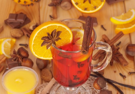 Mulled wine with orange, a jar of honey, nuts and sweets on a background of light wood.