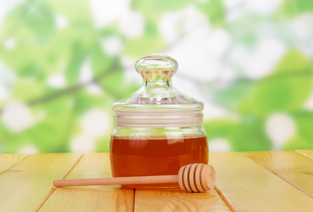 wooden scoop: Glass jar with honey and wooden scoop on an abstract green background. Stock Photo