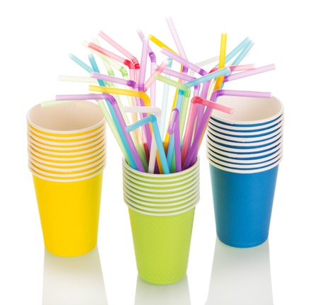 Colored disposable paper cups and straws isolated on white background.