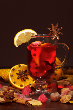 Mulled wine with orange, cloves, anise and cinnamon on a brown background.