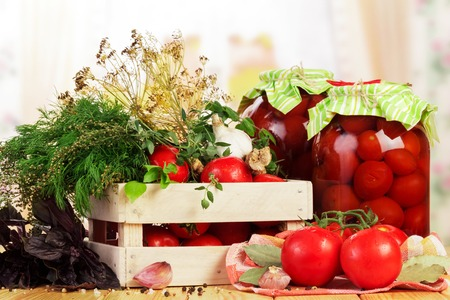 Wooden box with tomatoes, jars of marinated and spices isolated on white background.