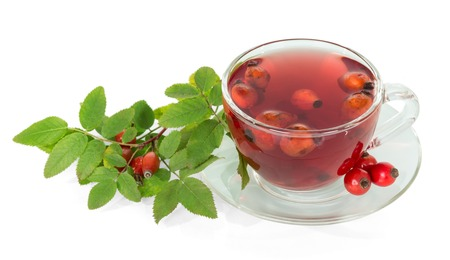 wild rose: Branch with berries of wild rose and cup of tea isolated on white background.