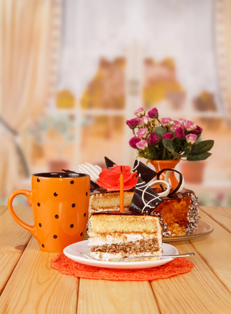 Chocolate cream cake, cup of tea, a slice, a candle on the background of the kitchen.