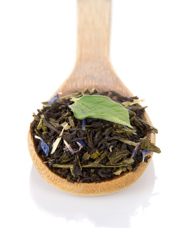 caffeine free: Fragrant dry tea with cornflowers and green leaf in a wooden spoon isolated on white background.