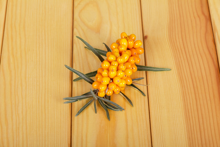 seabuckthorn: Bunch of ripe sea-buckthorn berries on a background of light wood. Stock Photo