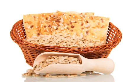 wooden scoop: Basket with peeled sunflower seeds and biscuits, wooden scoop isolated on white background. Stock Photo