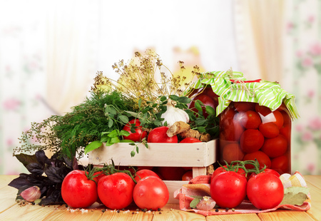 Box of fresh tomatoes and jars of pickled spices isolated on a white background. Stock Photo