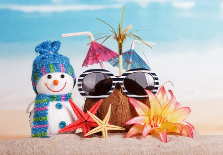 holiday greeting: Christmas snowman, coconut glasses, flowers and starfish in the sand on background of ocean